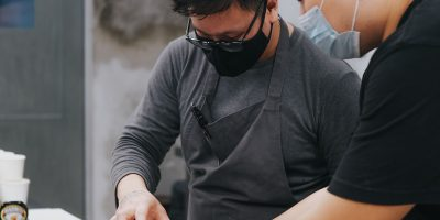 Preparing food in a kitchen with protective face masks