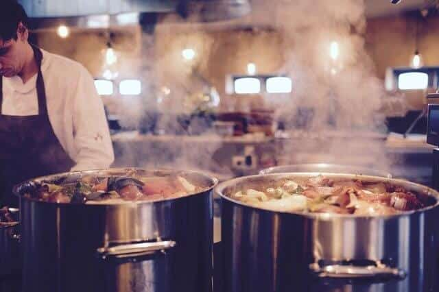 Chef preparing food next to two boiling cooking pans