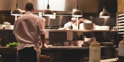 Head Chef looking into busy kitchen from over the serving counter